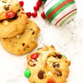 4 cookies sitting on a white marble table topped with M&Ms, Christmas calls on table with red cranberries.