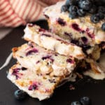 Blueberry loaf on slate plate, plate containing sliced blueberry loaf.