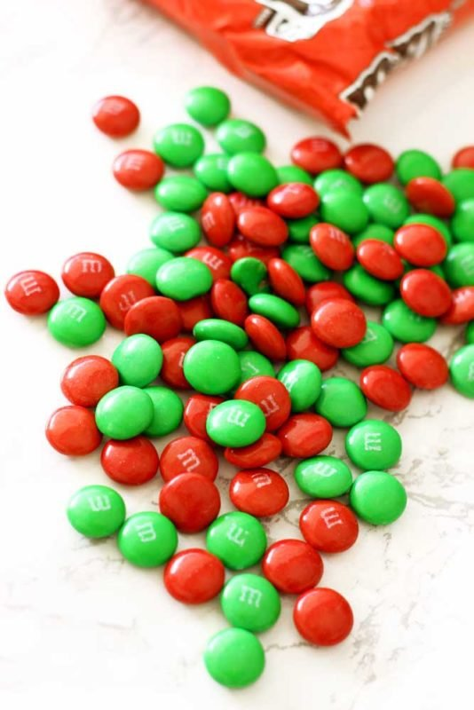 Bag of red and green M&Ms sitting on a white marble table.
