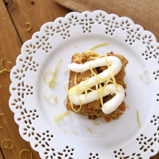 Lace white place containing a Carrot and Zucchini Bars with Lemon Cream Cheese Frosting sitting on a brown table, topped with lemon zest and fork on side of plate. Glass of milk in background.