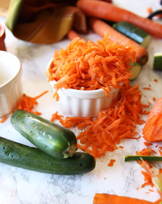 White ramekin containing shredded carrots and zucchini on a white marble table.