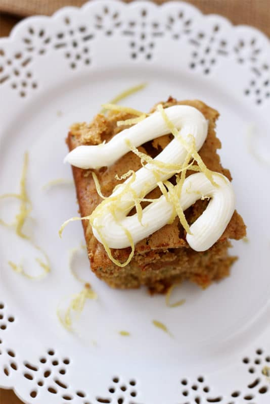 Lace white place containing a Carrot and Zucchini Bars with Lemon Cream Cheese Frosting topped with lemon zest.