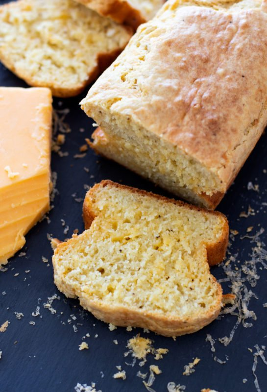Peppeyr Cheese Bread Loaf with a sliced piece of bread on cutting board.