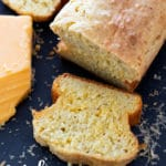 Pepper Cheese Bread Loaf with a sliced piece of bread on cutting board.