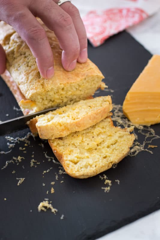 Person slicing bread with knife, sharp cheddar cheese block on table.