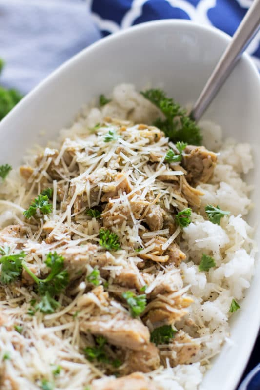 White dish containing Pesto Chicken Thighs on a bed of rice topped with fresh Parmesan and fresh chopped parsley, fork in bowl.