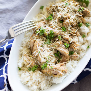 Chicken Pesto Thighs sitting in a white dish served over white rice topped with fresh parsley and Parmesan cheese.