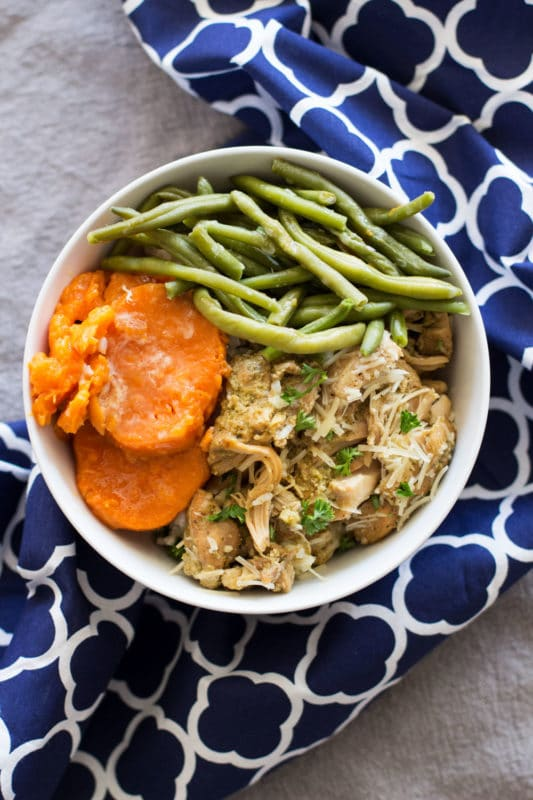White bowl containing Chicken Pesto Thighs, sliced yams and green beans, blue and white chevron napkin on table.
