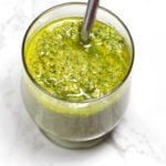 Jar of green dairy free pesto sauce on a white marble table, spoon in jar.