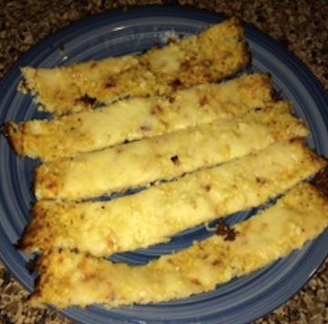 A blue plate of five cheesy garlic cauliflower breadsticks.