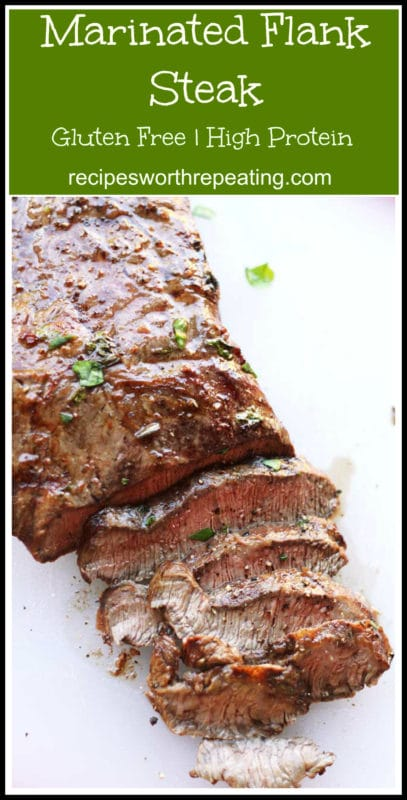 Marinated and grilled slices of flank steak sitting on a white table, topped with fresh parsley and ground pepper.