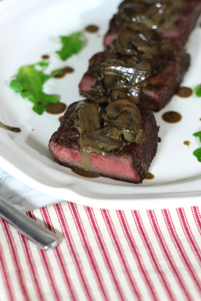 A close up of steak and mushrooms drizzled with a creamy balsamic mushroom sauce.