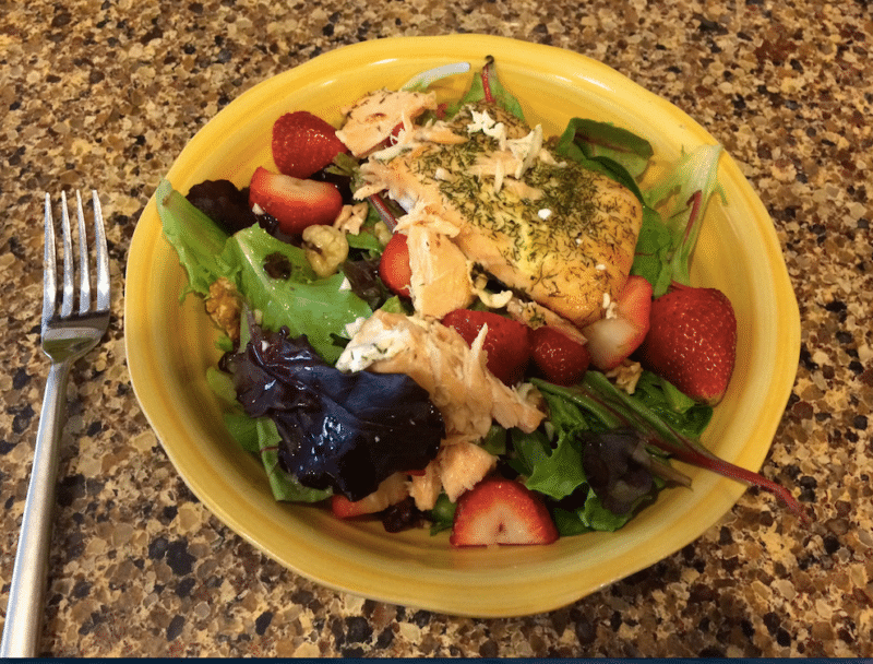 A bowl of mixed green salad with salmon, cut strawberries, and white wine dressing on a counter.