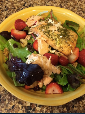 A yellow bowl of mixed salad with salmon, cut strawberries, and white wine dressing.