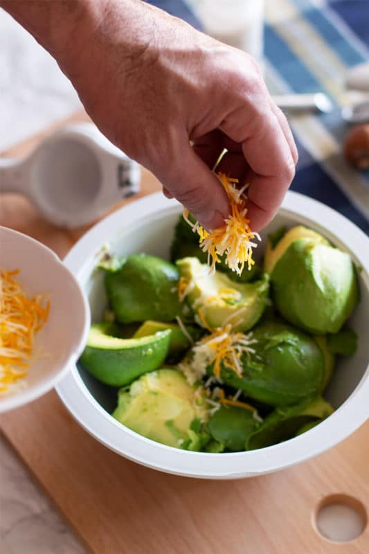 Man sprinkling shredded cheese into a bowl of avocados.