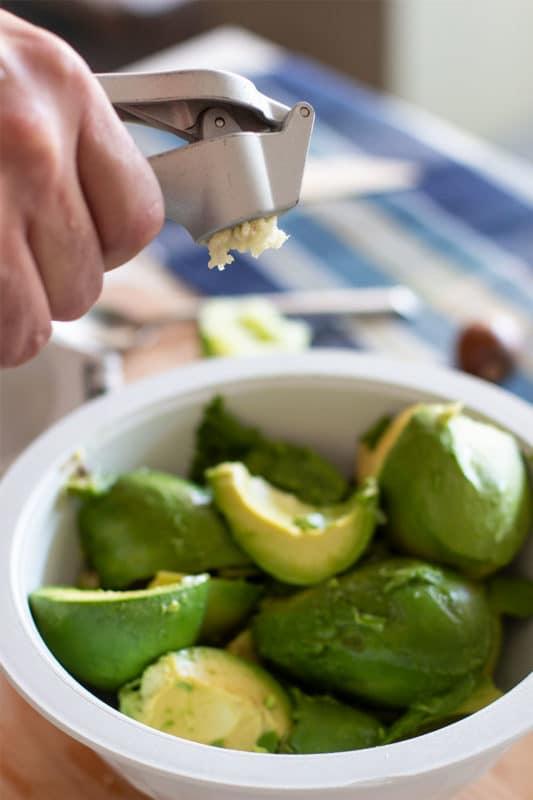 Man squeezing a garlic press into a bowl of fresh sliced avocados.