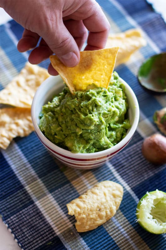 Man dipping a tortilla chip into a bowl of guacamole, chips and lime slices on table.