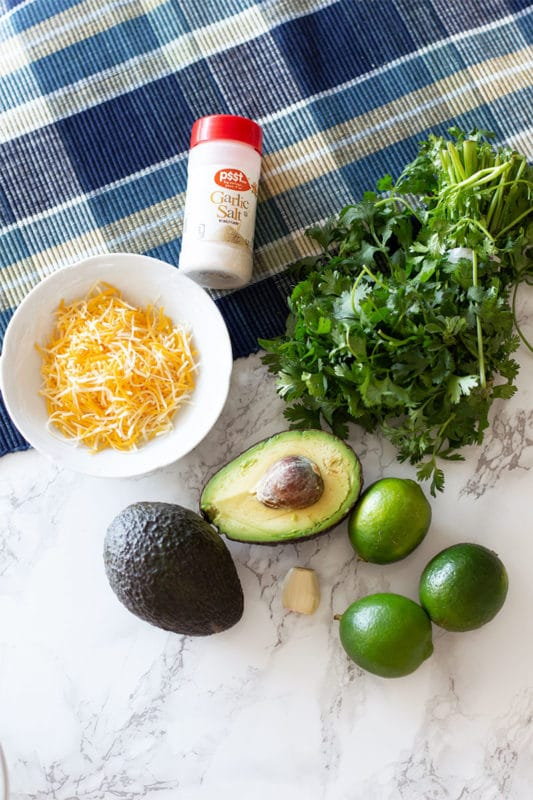Fresh ingredients to make homemade guacamole, cilantro, avocado, limes, garlic, cheese and garlic salt.