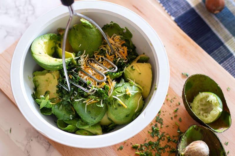 White bowl containing avocados, cilantro, garlic, onions and lime.