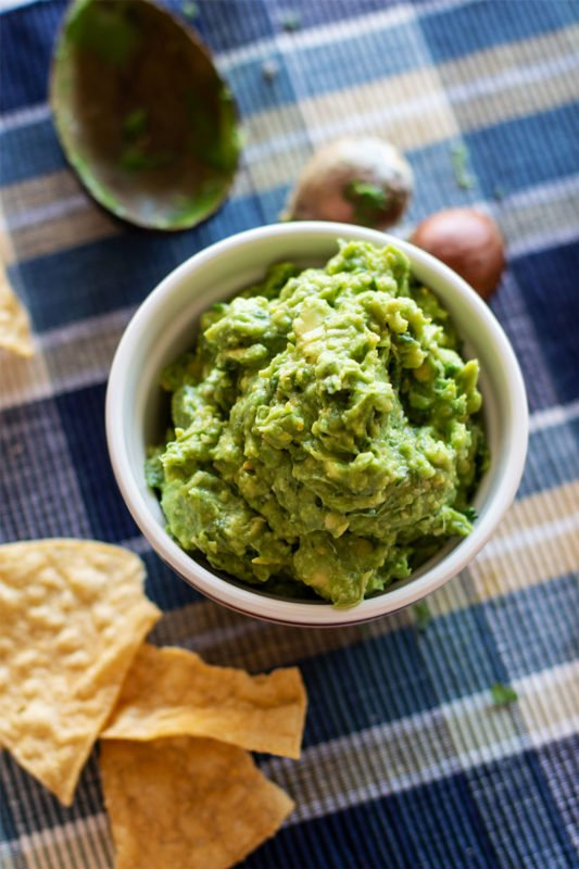 White bowl containing homemade guacamole sitting on a blue tablecloth, tortilla chips on table.
