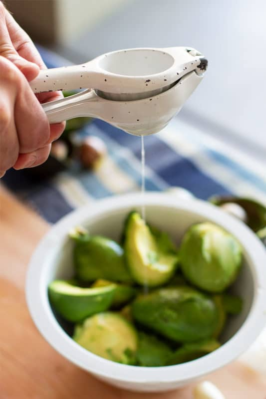 Man squeezing a citrus press and lime juice being added to a bowl of freshly cut avocados.