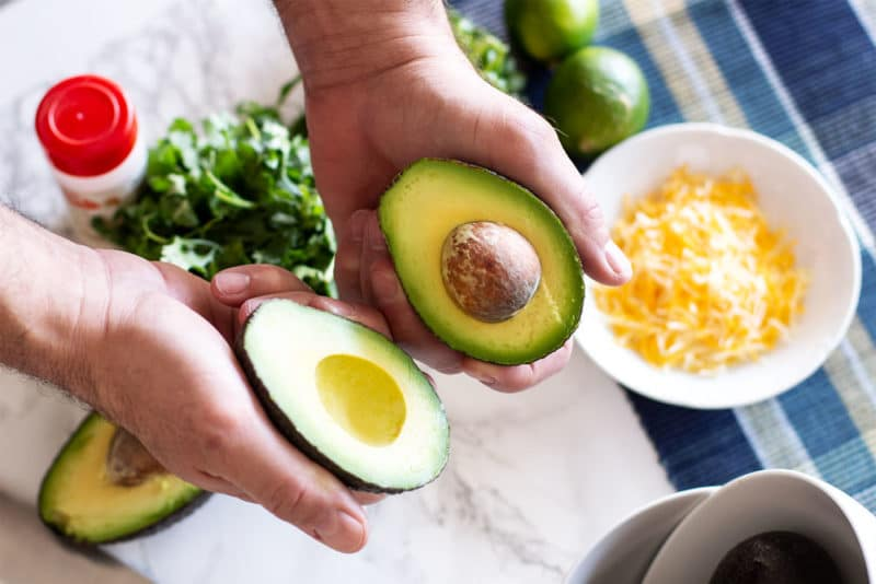 Hands displaying a sliced avocado opened up with pit.