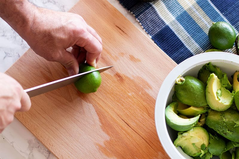 Man's hand slicing a lime on a wooden cutting board. Bowl of fresh avocado on table.