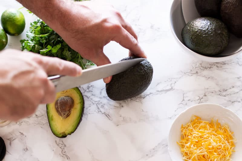 Man's hand slicing an avocado on a white marble table, shredded cheese and cilantro on table.
