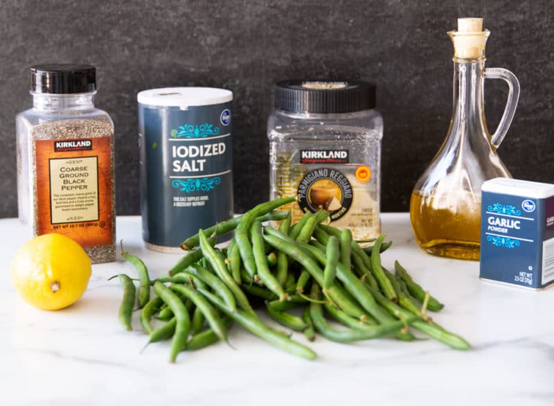Fresh green beans, lemon, garlic powder, olive oil, Parmesan cheese, and salt on a marble table.