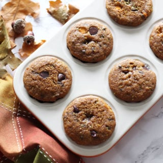 White muffin tin containing 6 Pumpkin Chocolate Chip muffins, napkin, leaves and acorns on table.