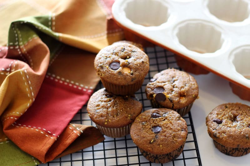 6 Pumpkin Chocolate Chip Muffins sitting on a black wire cooling rack, napkin and muffin pan in background.