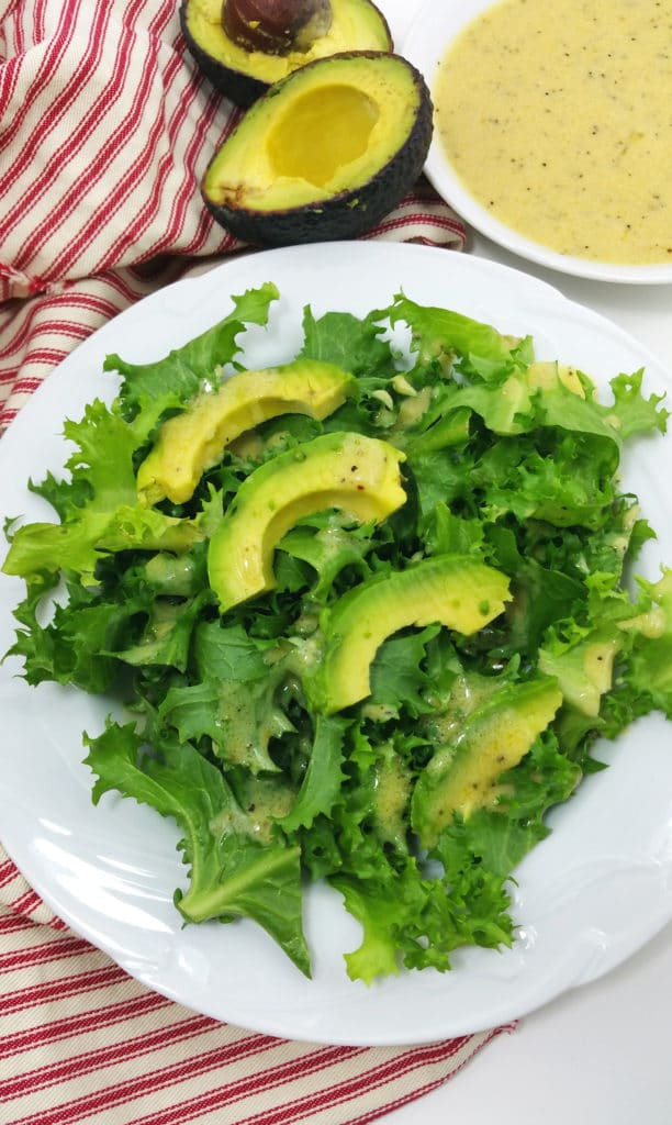 Endive Salad on a white plate, topped with fresh sliced avocado, dressing on side with red and white napkin on side.