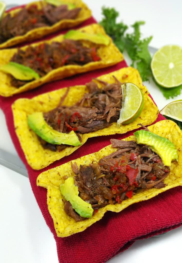 Crock Pot Beef Carnitas Tacos toped with avocado and lime wedges.