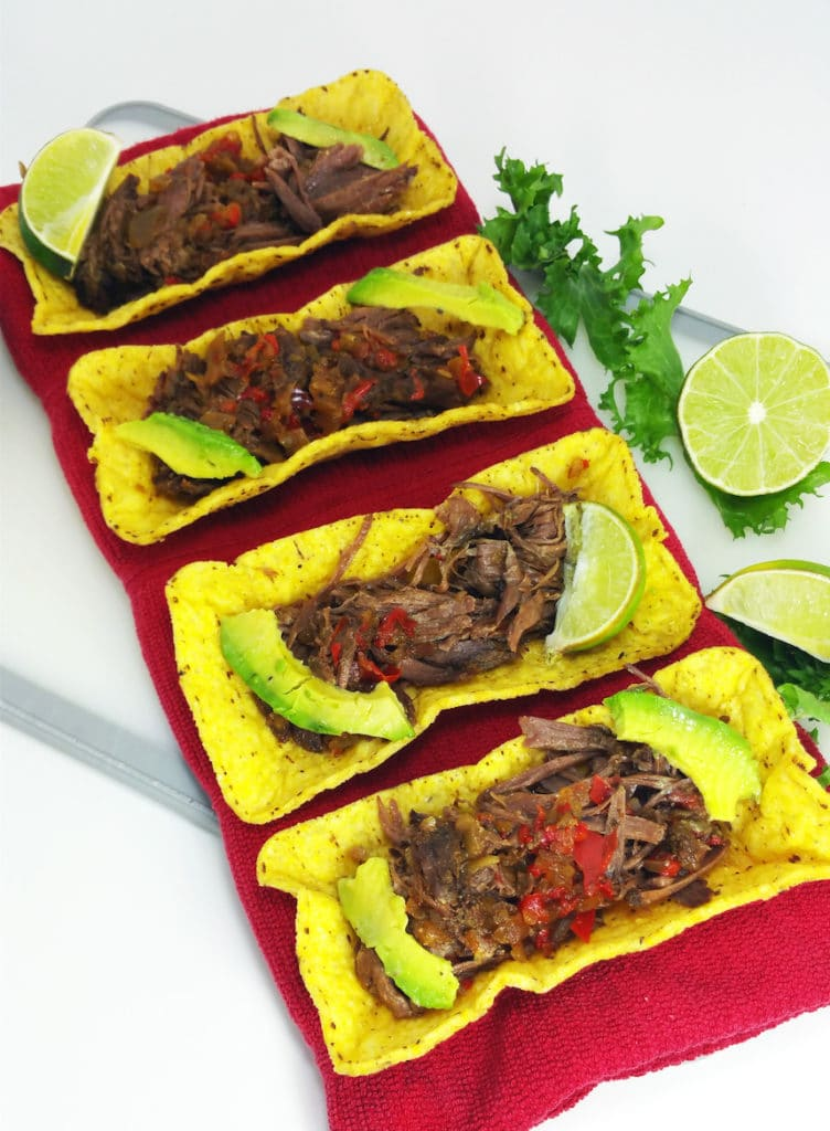 4 Crock Pot Beef Carnitas Tacos toped with avocado on a red napkin on a white table, limes on side.