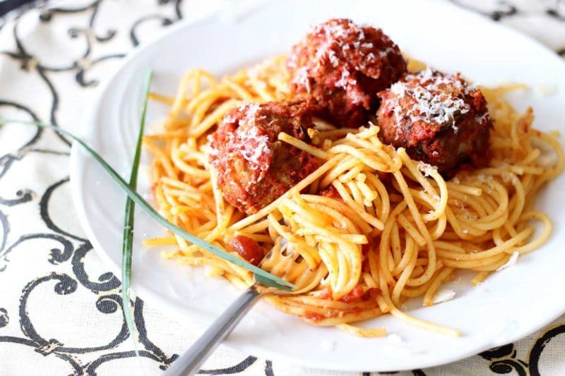 White plate containing spaghetti noodles, three meatballs and marinara sauce, fork in the noodles.