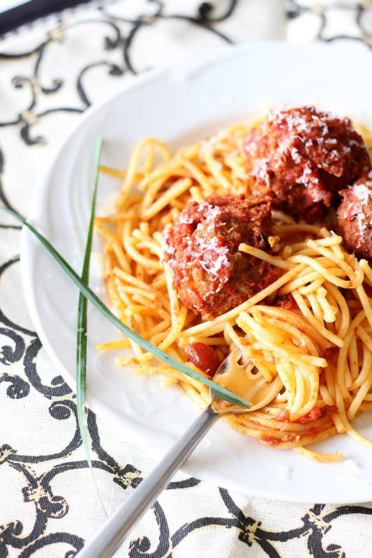 Three Meatballs sitting on top of spaghetti noodles with marinara sauce sitting on a white plate, fork and parsley.