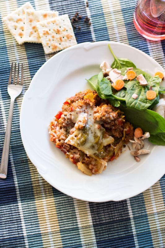 White plate containing Cabbage Roll Casserole sitting on a blue placemat, served with a spinach salad, fork and crackers on table.