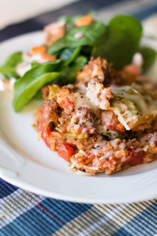 White plate containing Cabbage Roll Casserole served with a spinach salad.