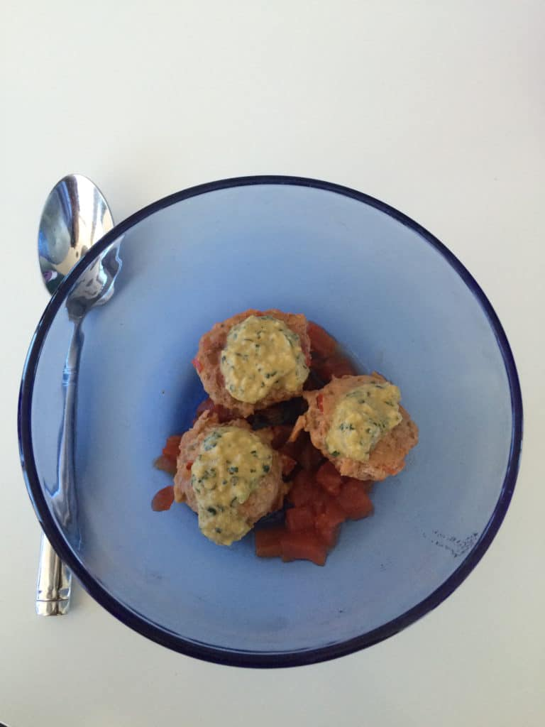A clear blue bowl contacting three southwest meatballs next to a silver spoon on a table.