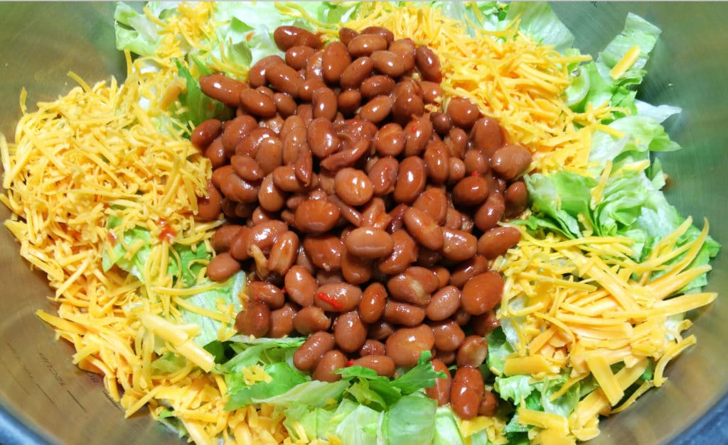A close up of beans, shredded cheese, on a bed of chopped iceberg lettuce.