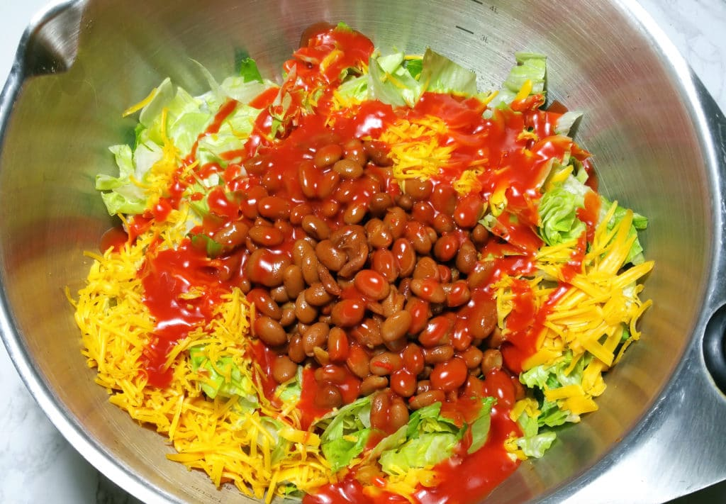 A bowl of beans, shredded cheese, on a bed of chopped iceberg lettuce cover with Catalina Dressing.