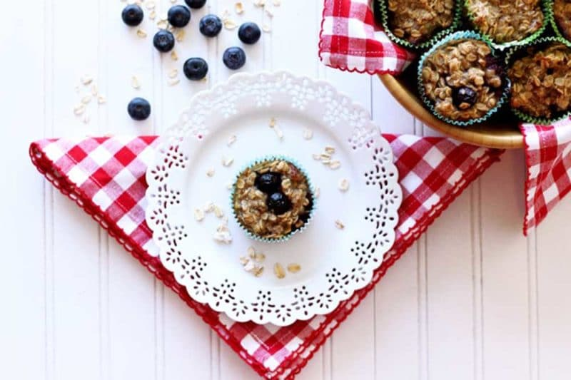 Baked blueberry oatmeal cupcake sitting on a white plate, with a red and white napkin, a bowl of cupcakes sitting on a white table.