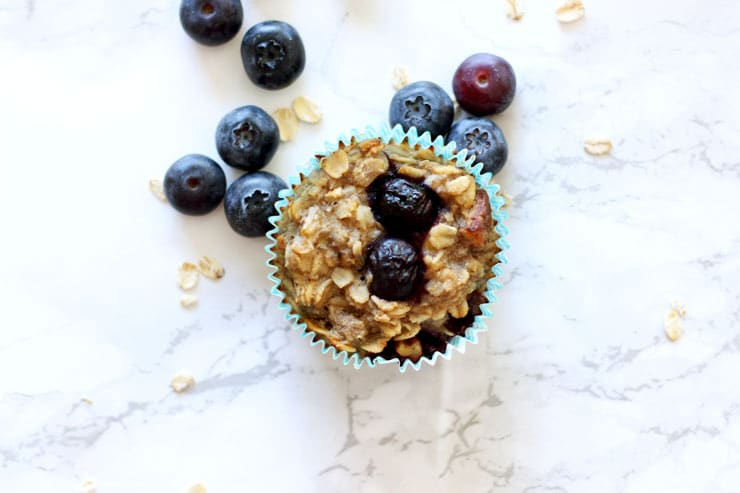 Baked blueberry oatmeal cupcake sitting on a white table with blueberries and oats.