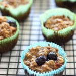 Baked Blueberry Oatmeal Cupcake in a blue cupcake wrapper cooling on a black wire rack.