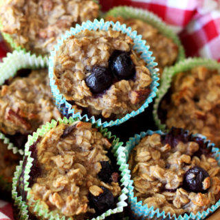 Brown bowl with a red and white checkered napkin containing 7 Baked Oatmeal Blueberry Oatmeal Cupcakes.