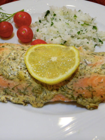 A white plate with roasted salmon, rice, cherry tomatoes on a table.