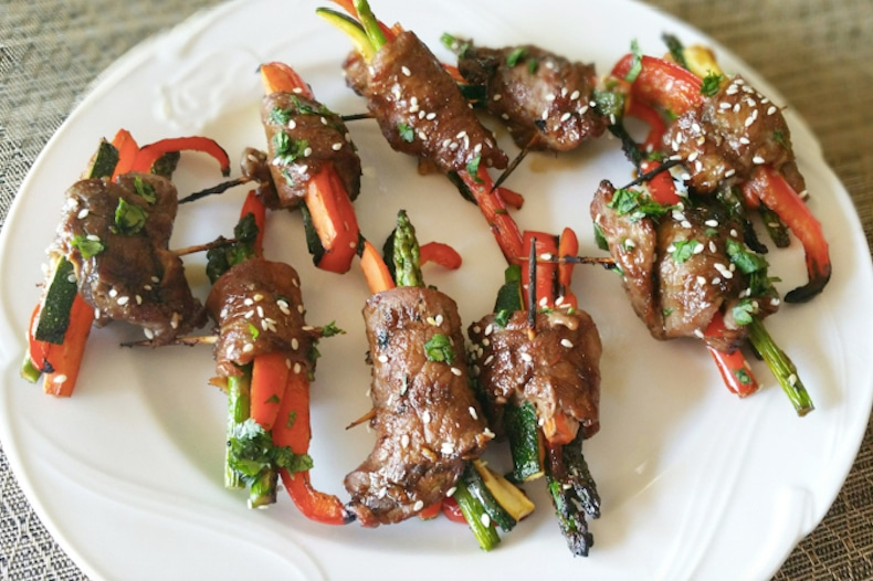 9 Asian Steak Roll Ups containing sirloin steak, carrots, asparagus and zucchini sitting on a white plate.