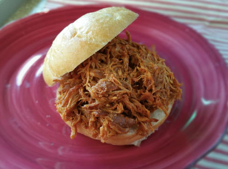Red plate containing a BBQ pulled chicken sandwich on a kaiser roll.