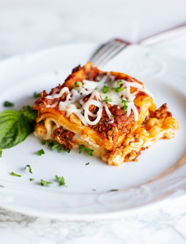 White plate containing a slice of layered lasagna with Italian meat sauce and 4 cheeses. Topped with with basil.