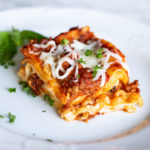 White plate containing a slice of cooked7 layered lasagna with an Italian meat sauce topped with melted mozzarella cheese and fresh basil.